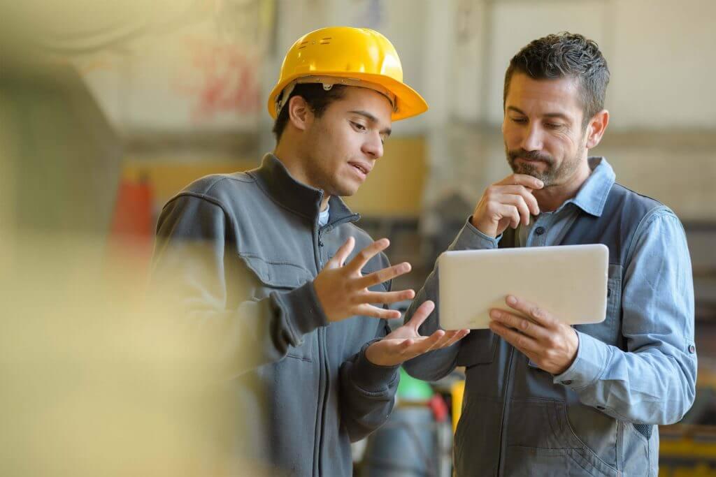 2 men in work looking at tablet screen