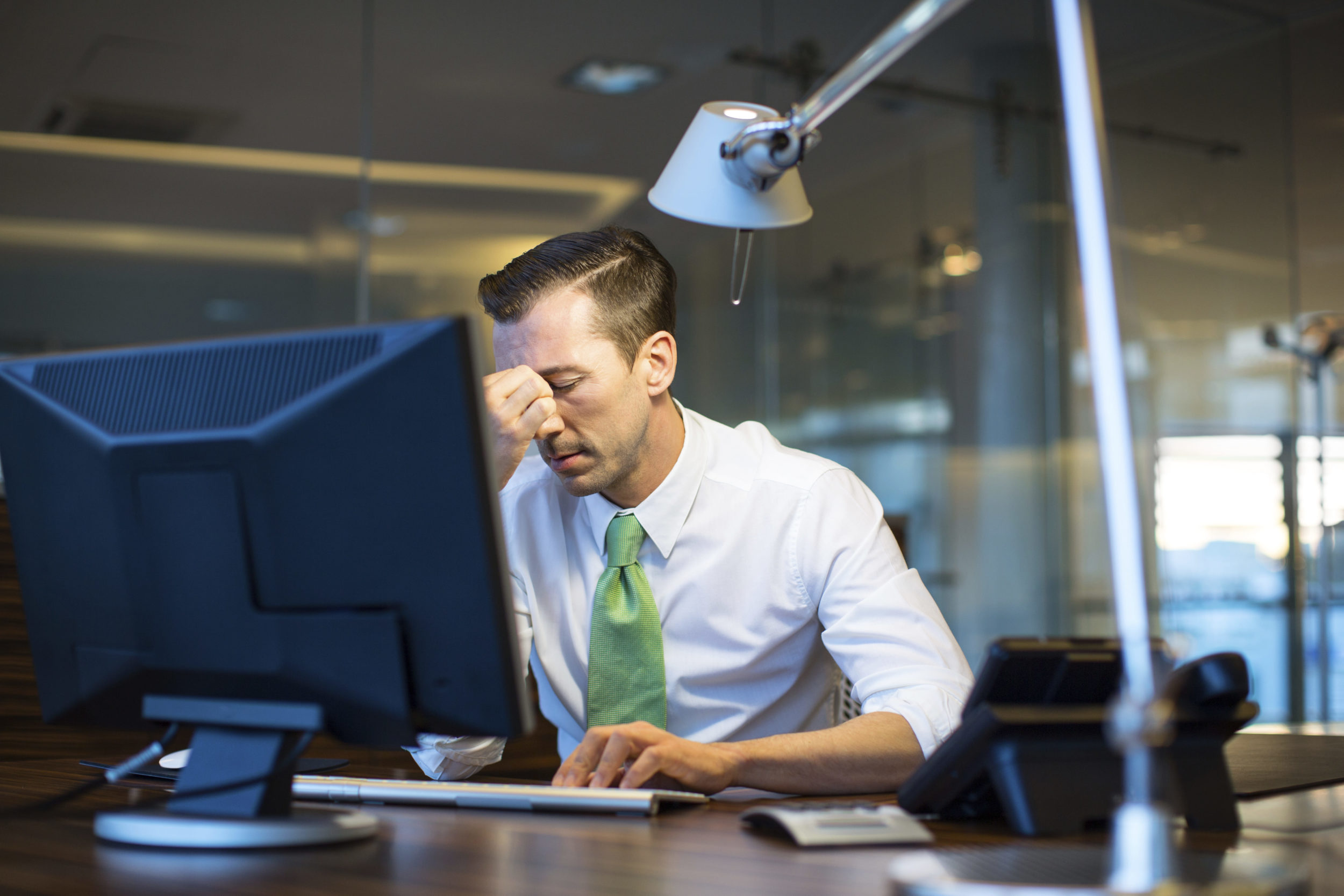 Business man at desk with his head in his hand